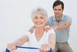 Male therapist assisting senior woman with exercises