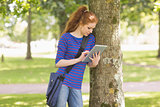 Redhead student leaning against a tree using her tablet pc