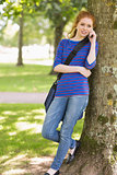Redhead student leaning against a tree talking on the phone