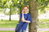 Cheerful student leaning against a tree talking on the phone