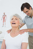 Male physiotherapist massaging a senior woman's shoulders