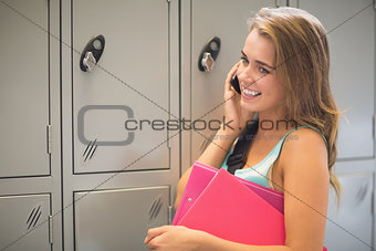 Pretty student talking on the phone beside lockers