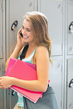 Smiling student talking on the phone beside lockers