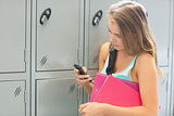 Smiling student sending a text beside lockers