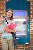 Happy student standing showing her card to camera at the atm