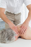Physiotherapist massaging a senior woman's back
