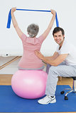 Senior woman on yoga ball with a physical therapist