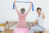 Therapist gesturing thumbs up by woman on yoga ball