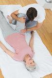 Physical therapist examining senior woman's leg