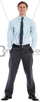 Smiling businessman standing with hands in pockets