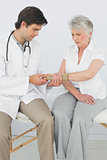 Male physiotherapist examining a senior woman's wrist