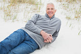 Smiling senior man relaxing on sand at beach