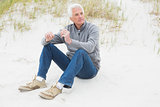 Casual senior man relaxing on sand at beach