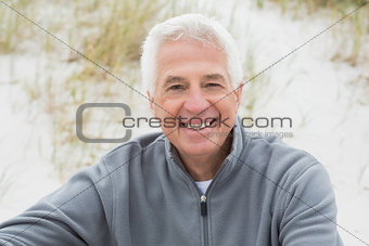 Smiling casual senior man relaxing at beach