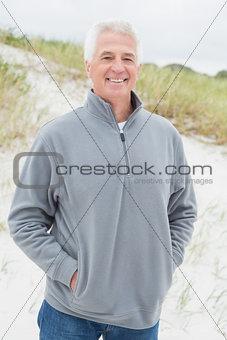 Portrait of smiling casual senior man at beach