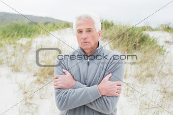 Casual senior man feeling cold at beach