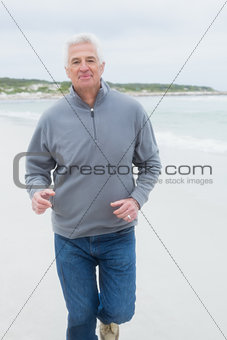 Portrait of a senior man running at beach