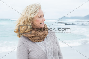 Contemplative senior woman looks away at beach
