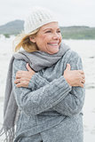 Cheerful senior woman shivering at beach