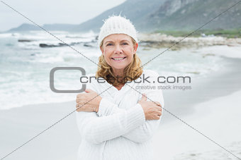 Happy senior woman feeling cold at beach