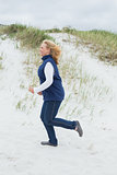 Side view of a senior woman jogging at beach