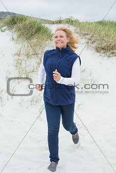 Happy senior woman jogging at beach