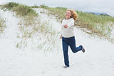 Happy senior woman running at beach