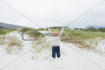 Senior woman jumping at beach