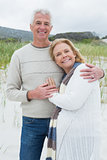 Happy senior man embracing woman at beach
