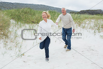Cheerful senior couple running at beach