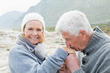 Senior man kissing happy woman's hand