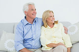 Senior couple sitting on sofa while looking away