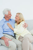 Happy romantic senior couple sitting on sofa
