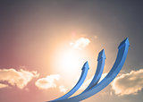 Blue curved arrows pointing up against sky