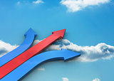 Red and blue joined arrows pointing against sky