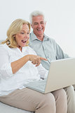 Cheerful senior couple using laptop at house