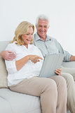 Relaxed senior couple using digital tablet on sofa