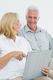 Relaxed senior couple using digital tablet at house