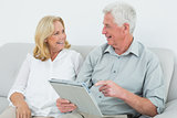 Relaxed senior couple using digital tablet at home
