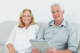 Relaxed senior couple with digital tablet at home