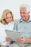 Relaxed happy senior couple using digital tablet