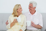 Loving senior couple with coffee cups at home