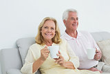 Relaxed senior couple with coffee cups at home