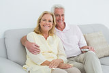 Relaxed happy senior couple with remote control at home