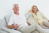 Senior couple with remote control at home