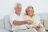 Cheerful senior couple watching television