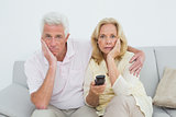 Shocked senior couple watching television