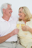Senior couple with champagne flutes at home