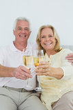 Senior couple holding out champagne flutes at home
