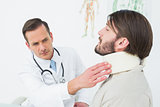 Male doctor examining a patient's neck